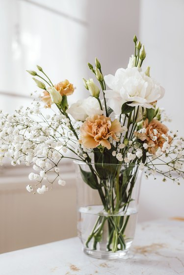 Glass vase with peach and white flowers