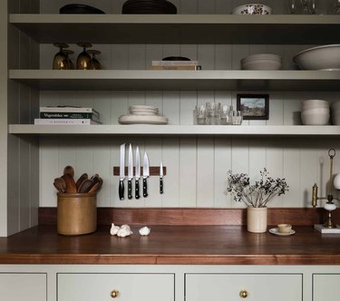 Olive green kitchen cabinets with wood counters and olive green shiplap