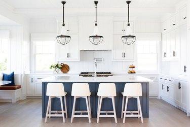 White kitchen with gray island, white shiplap backsplash, large pendant lights