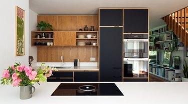 Modern kitchen with black cabinets and wood backsplash