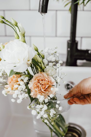 Adding water to glass vase with flowers