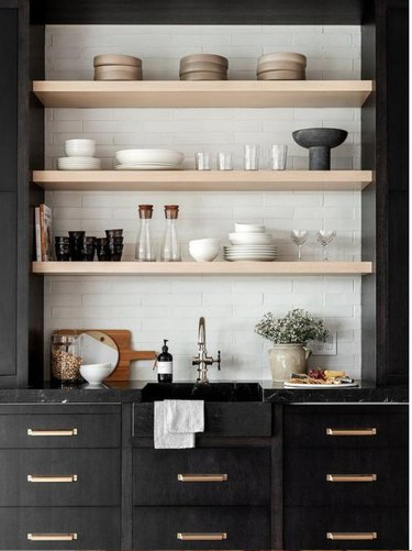 black cabinets, white tile and bleached wood shelving