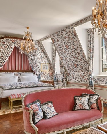room inside Versailles hotel with pink furniture, floral wallpaper, and chandeliers