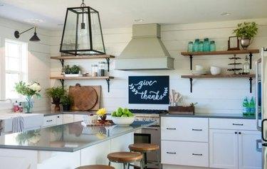 White farmhouse kitchen, island, large pendant light, white cabinets