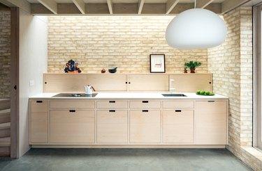Modern kitchen with light wood cabinets and backsplash