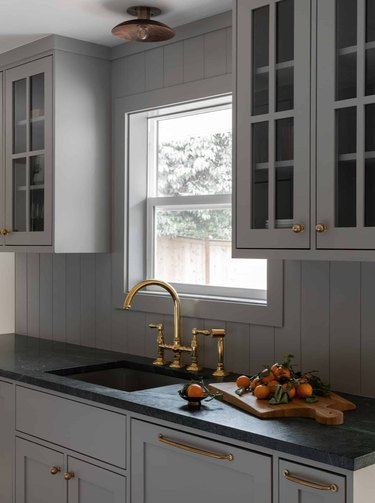Gray kitchen cabinets with matching gray shiplap backsplash, brass faucet, dark counters