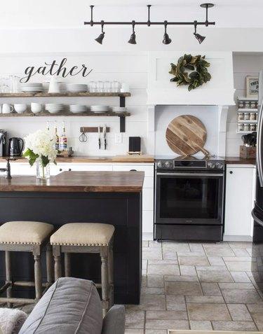 White kitchen corner with black oven, hardware, and refrigerator