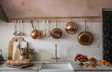 pink and white kitchen with copper pots hanging from a rack