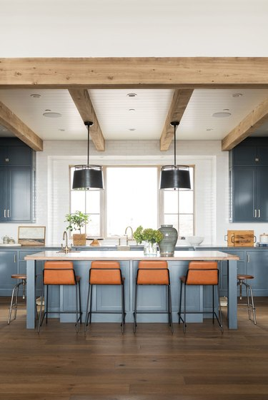 light navy blue kitchen with cognac bar stools around island