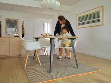 a kid and adult at the table with a rug underneath and framed art on the wall