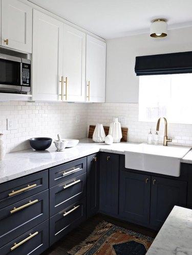 dark navy blue cabinets with vintage rug and white subway tile backsplash