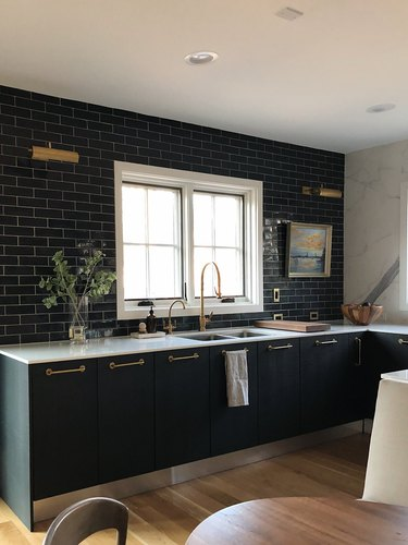 all black kitchen with white counter and wood floors