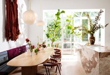 white kitchen with pink marble island and wooden table