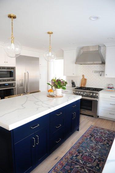 blue kitchen island with white marble top in modern kitchen