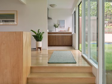 photo of hallway near glass windows and rug and plant