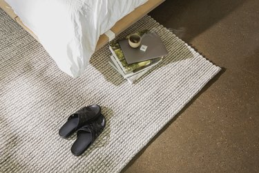 overhead photo of bed near rug and slippers and books