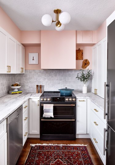 modern kitchen with pink walls and white cabinets