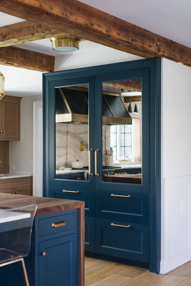 navy blue pantry doors with wood beams in white kitchen
