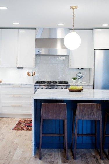 blue kitchen island with waterfall countertop and globe pendant light