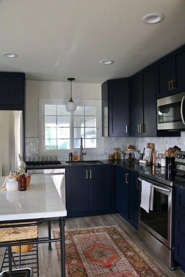 dark navy kitchen cabinets with vintage rug and marble backsplash