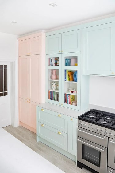 white and blue kitchen with pink accent cabinet