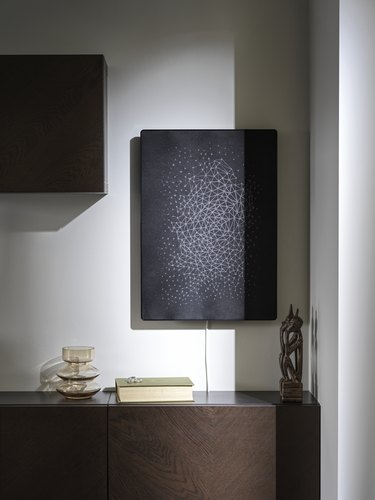 brown furniture piece with black speaker mounted on the wall