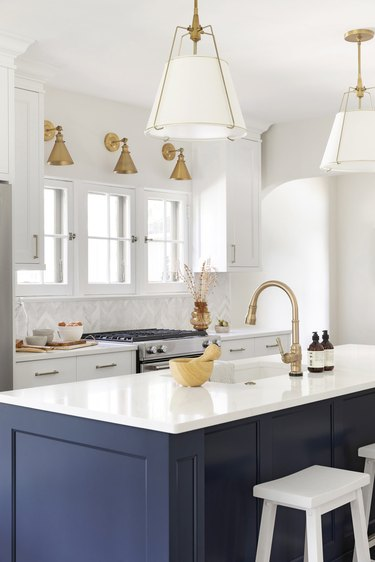 navy blue island with brass lighting and white countertop
