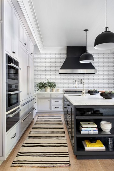 white kitchen with black grout lines and black pendant lights