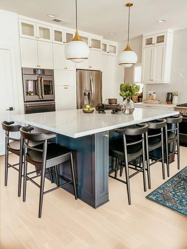 navy blue kitchen island with black chairs with globe pendant lights