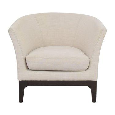 barrel chair in cream color with dark legs