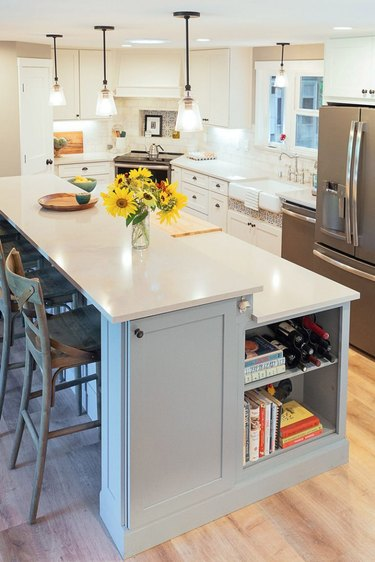 blue two-tier kitchen island with kitchen cabinet and shelving