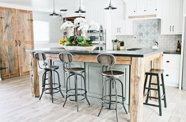 rustic wood and light green two-tier kitchen island with industrial bar stools