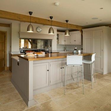 beige two-tier kitchen island with cabinets under bar