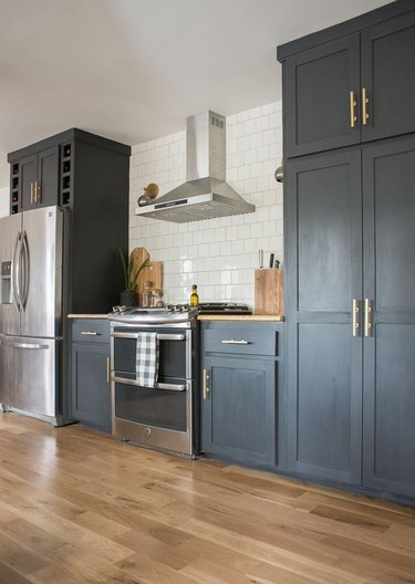 navy blue kitchen cabinets with stove and stainless steel appliances