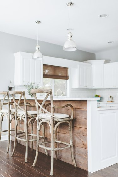 white and reclaimed wood two-tier kitchen island with wood bar stools