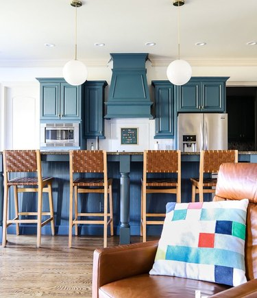 navy blue kitchen with accompanying living room and pendant lights