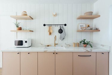 pink kitchen cabinets with black hardware and marble countertop
