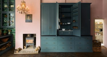 pink kitchen with blue cabinets and crystal chandelier