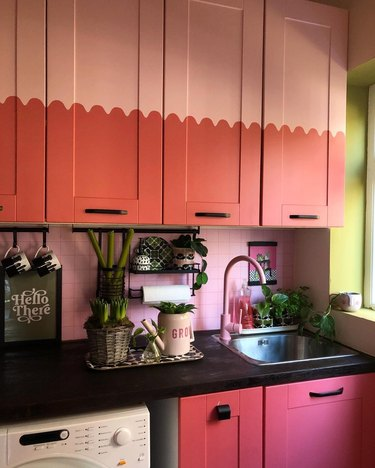 kitchen with pink and salmon cabinets and faucet and plants