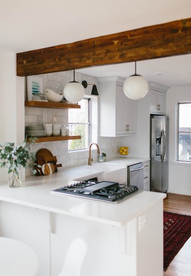 white midcentury l-shaped kitchen with wood beams