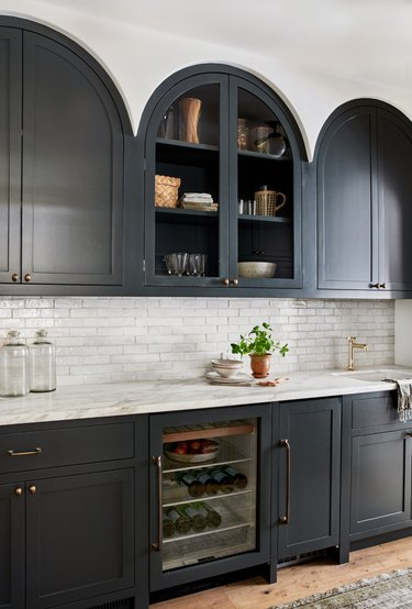 black and white kitchen with arched upper cabinet design