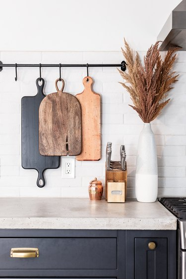 cutting boards hanging from rod in industrial farmhouse kitchen
