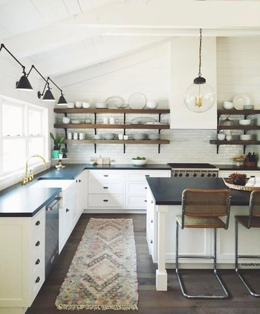 industrial farmhouse kitchen with white cabinets and black countertops