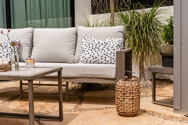couch and chair on outside patio with plant