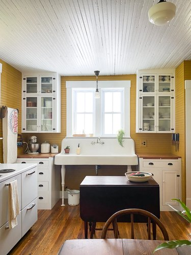 yellow and white industrial farmhouse kitchen with large sink