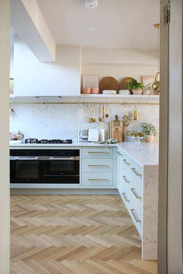 white l-shaped kitchen with open shelf and rod for cooking tools