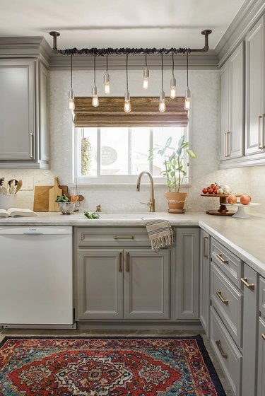 gray and white l-shaped kitchen with chandelier over sink