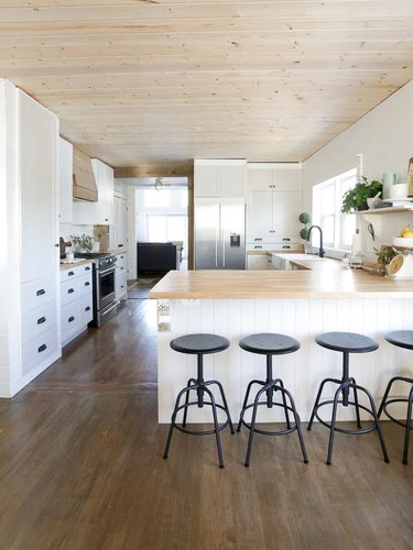 white and wood l-shaped kitchen with black bar stools