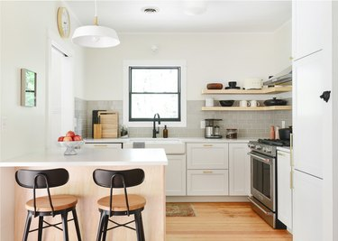 small l-shaped kitchen with white cabinets and bar