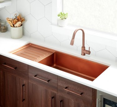 Copper undermount drainboard sink with copper faucet, white counters.